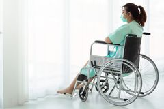 Donna asiatica che si siede su una sedia a rotelle che guarda fuori della finestra fotografia stock