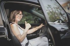 Donna asiatica che si siede sul sedile del conducente tumb di sospiro dell'automobile del suv nel buon immagini stock libere da diritti