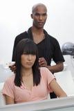 Donna asiatica che si siede sulla sedia con il parrucchiere che sta dietro immagine stock