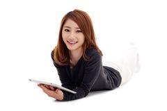 Donna asiatica che si trova giù con il PC della compressa Fotografia Stock