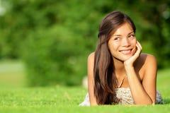 Donna asiatica che si trova nell'erba Fotografia Stock