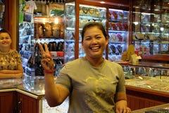 Donna asiatica che sorride e che gesturing, venditore dei gioielli fotografia stock