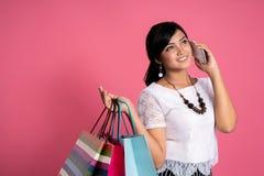 Donna asiatica che tiene i sacchetti della spesa e telefono fotografia stock