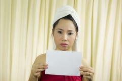 Donna asiatica che tiene insegna in bianco vuota ed agire porta una gonna per coprire il suo seno dopo i capelli del lavaggio, av immagine stock