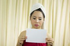 Donna asiatica che tiene insegna in bianco vuota ed agire porta una gonna per coprire il suo seno dopo i capelli del lavaggio, av fotografia stock