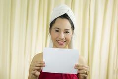 Donna asiatica che tiene insegna in bianco vuota ed agire porta una gonna per coprire il suo seno dopo i capelli del lavaggio, av fotografia stock libera da diritti