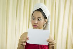 Donna asiatica che tiene insegna in bianco vuota ed agire porta una gonna per coprire il suo seno dopo i capelli del lavaggio, av immagine stock libera da diritti