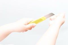 Donna asiatica che tiene un coltello giallo della taglierina della scatola fotografia stock