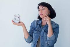 Donna asiatica che tiene una sveglia rosa su un fondo bianco Il concetto della gestione di tempo ottenga il controllo della vostr Fotografia Stock Libera da Diritti