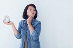 Donna asiatica che tiene una sveglia rosa su un fondo bianco Il concetto della gestione di tempo ottenga il controllo della vostr Immagine Stock
