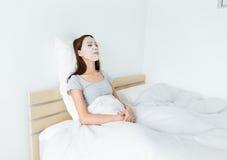 Donna asiatica che usando maschera di carta sul fronte e riposandosi sul letto Fotografia Stock Libera da Diritti