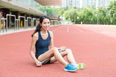 Donna asiatica che utilizza il bastone di massaggio del rullo nello stadio di sport Fotografia Stock