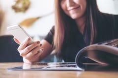 Donna asiatica che utilizza Smart Phone mentre libro di lettura nel caffè dei bistrot con il fronte sorridente fotografia stock
