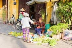 Donna asiatica che vende i caschi di banane nel mercato di strada Fotografia Stock