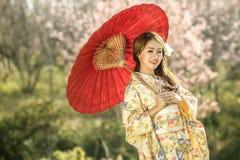 Donna asiatica con il camaleonte tradizionale del vestito e l'ombrello rosso Fotografia Stock Libera da Diritti