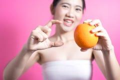 Donna asiatica con il concetto arancio Lei che sorride e che tiene arancia Fronte di bellezza e trucco naturale Isolato sopra fon fotografie stock
