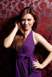 Donna asiatica con il vestito viola Immagine Stock