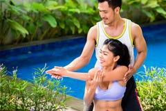 Donna asiatica con l'istruttore all'allenamento di forma fisica Fotografia Stock