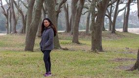 Donna asiatica con la condizione del parka davanti agli alberi fotografie stock