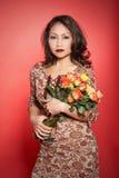 Donna asiatica con le rose. Fotografie Stock