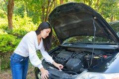 Donna asiatica con un'automobile rotta con il cappuccio aperto Fotografia Stock