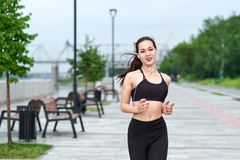 Donna asiatica corrente sul lungomare Pareggiare di mattina I treni dell'atleta immagine stock libera da diritti