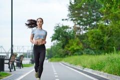 Donna asiatica corrente sul lungomare Pareggiare di mattina I treni dell'atleta immagini stock libere da diritti