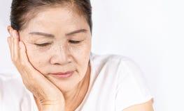 Donna asiatica corrugata anziana che pensa con lo spazio della copia immagine stock
