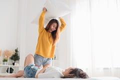 Donna asiatica del lesbain che gioca insieme volo del cuscino sul letto in whi immagine stock libera da diritti