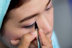 Donna asiatica del primo piano che applica eye-liner sull'occhio Fotografia Stock