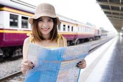 Donna asiatica del viaggiatore che esamina mappa il destinati del ritrovamento della stazione ferroviaria fotografia stock