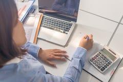 Donna asiatica dell'ufficio che scrive nota nella stanza di affari immagini stock libere da diritti