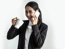 Donna asiatica di affari di bellezza in vestito convenzionale che tiene una tazza di caffè in suoi mano e telefono che comunica s immagine stock libera da diritti