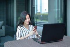 Donna asiatica di affari casuali che per mezzo di uno smartphone davanti ad un rivestimento Immagine Stock