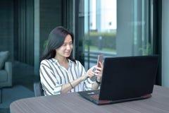 Donna asiatica di affari casuali che per mezzo di uno smartphone davanti ad un rivestimento Immagine Stock Libera da Diritti
