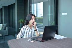 Donna asiatica di affari casuali che sbadiglia e che lavora davanti ad una La Fotografie Stock
