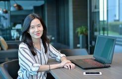 Donna asiatica di affari casuali che sorride davanti ad un computer portatile nel cond Fotografia Stock Libera da Diritti