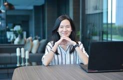 Donna asiatica di affari casuali che sorride davanti ad un computer portatile nel cond Immagini Stock Libere da Diritti