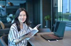 Donna asiatica di affari casuali che sorride e che legge un libro nella parte anteriore Fotografia Stock