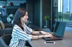 Donna asiatica di affari casuali che sorride e che utilizza un computer portatile nel condominio Fotografie Stock