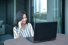 Donna asiatica di affari casuali che telefona davanti ad un computer portatile nel cond Fotografia Stock