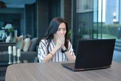Donna asiatica di affari casuali depressi che utilizza un computer portatile nell'hotel, g Immagine Stock Libera da Diritti