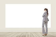 Donna asiatica di affari che esamina insegna in bianco immagini stock