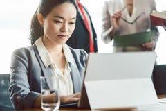 Donna asiatica di affari che lavora al computer portatile immagine stock