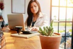 Donna asiatica di affari che per mezzo del calcolatore per la contabilità fotografia stock
