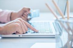Donna asiatica di affari che tiene una carta di credito e che per mezzo del computer portatile per l'acquisto online Immagine Stock