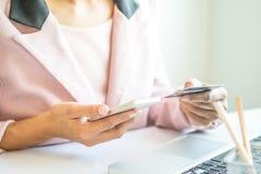 Donna asiatica di affari che tiene una carta di credito e che per mezzo dello smartphone per l'acquisto online Fotografie Stock Libere da Diritti