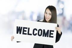 Donna asiatica di affari con capelli lunghi che tengono un bordo del segno positivo fotografia stock libera da diritti