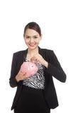 Donna asiatica di affari con la banca di moneta del maiale e della moneta Immagini Stock Libere da Diritti
