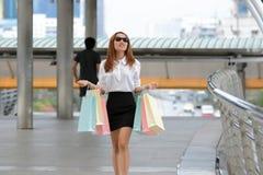 Donna asiatica di bellezza elegante con i sacchetti della spesa variopinti che cammina sulla via della città Fotografia Stock Libera da Diritti